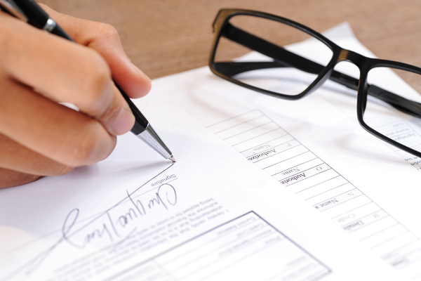 Closeup Of Person Signing Document. Contract And Glasses Lying On Table. Agreement Concept. Cropped View.