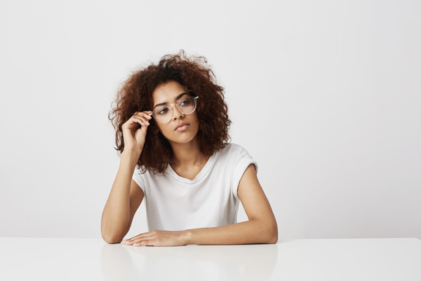 Dreamy Young Beautiful African Girl In Glasses Thinking Over White Background. Copy Space.